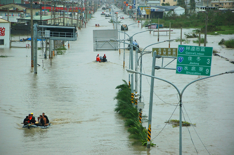 People get around central Linbian Township, Pingtung County, in boats yesterday after torrential rains brought by Typhoon Morakot. PHOTO: KUO CHING-HUI, TAIPEI TIMES